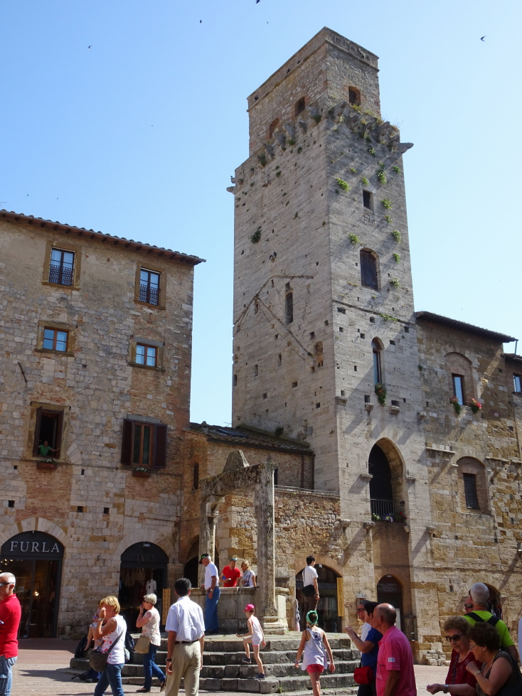 Piazza della Cisterna's namesake well and one of the towers