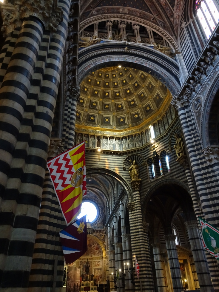 Inside Siena cathedral, note the district banners
