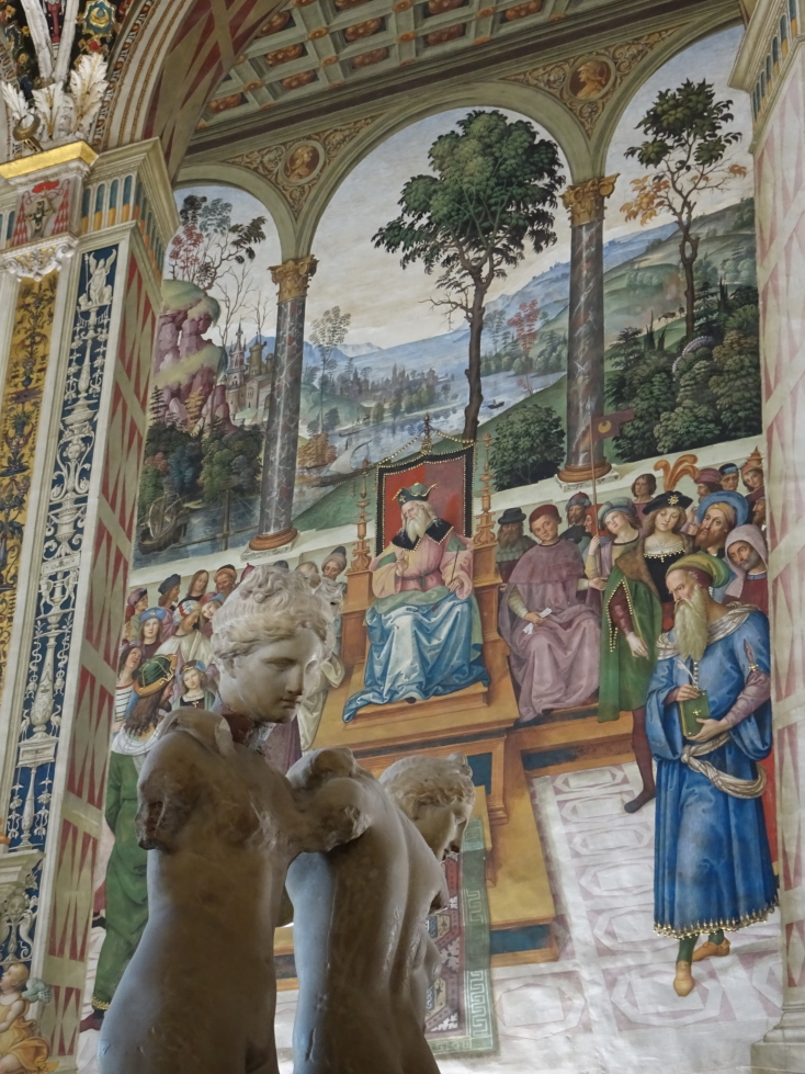 Another shot of the murals with statues in the foreground