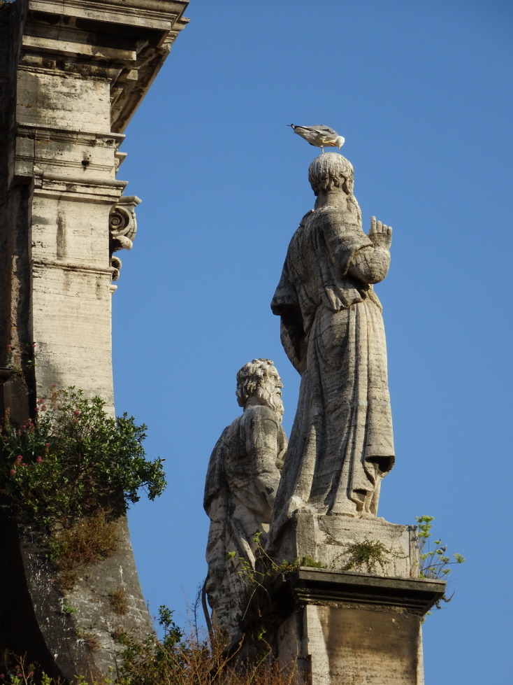 I couldn't resist this picture of a bird perched on a Saint