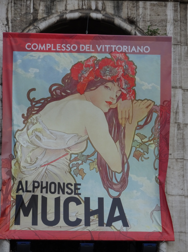 A sign advertising an Alphonse Mucha exhibition