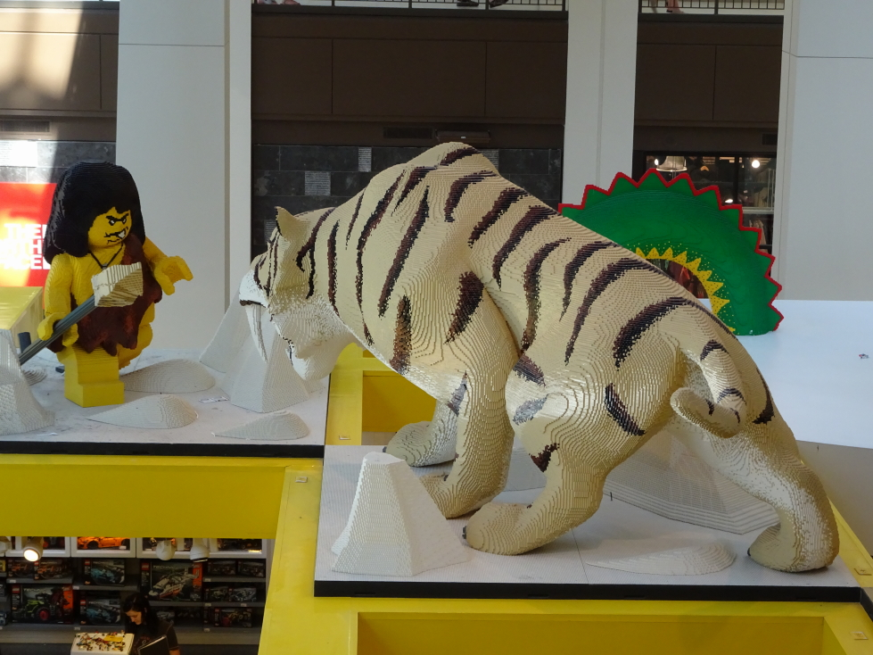A LEGO Neanderthal facing off against a saber-tooth tiger